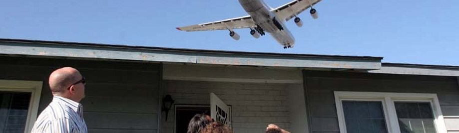 jet over house with family outside