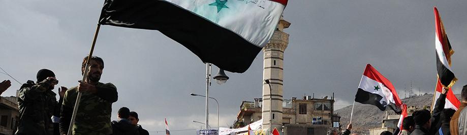 Οι υποστηρικτές του προέδρου Μπασάρ αλ-Άσαντ κύμα σημαίες της Συρίας κατά τη διάρκεια συγκέντρωσης στην πλατεία αλ-Sabaa Bahrat στη Δαμασκό