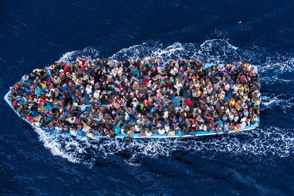 4 / Honderde vlugtelinge en immigrante aan boord van 'n vissersboot is uitgebeeld oomblikke voor deur die Italiaanse vloot gered word as deel van hul Mare Nostrum werking in Junie 2014. Onder onlangse en hoogs sigbare gevolge van konflikte in die wêreld, en die lyding wat hulle veroorsaak het, het 'n dramatiese groei in die aantal vlugtelinge soek veiligheid by die onderneming van gevaarlike see reise, insluitend op die Middellandse See was. Die Italiaanse kuswag / Massimo Sestini