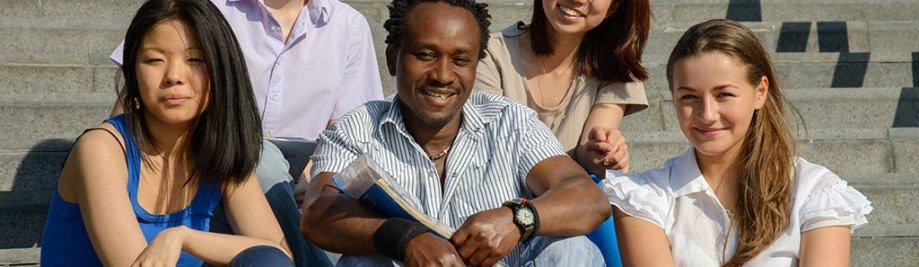 Multi-etniese groep van vyf universiteitstudente sit op trappe van Universiteit glimlag