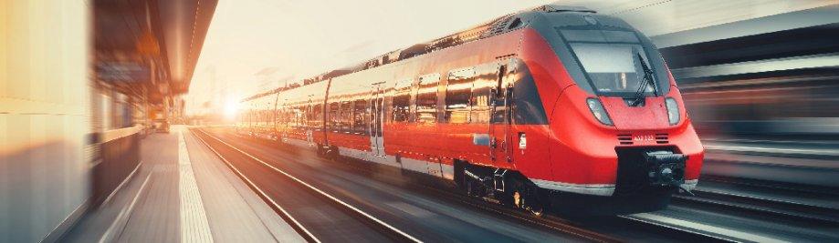 Piękna stacja kolejowa z nowoczesnym wysokiej prędkości czerwony pociąg podmiejski z efektem rozmycia ruchu w kolorowy zachód słońca w Norymberdze, Niemcy. Linia kolejowa z rocznika tonowaniem